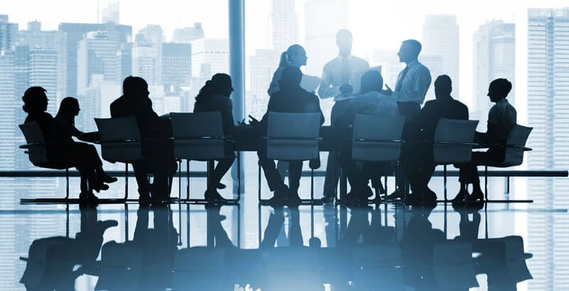 Many people sitting and standing around a table in a meeting