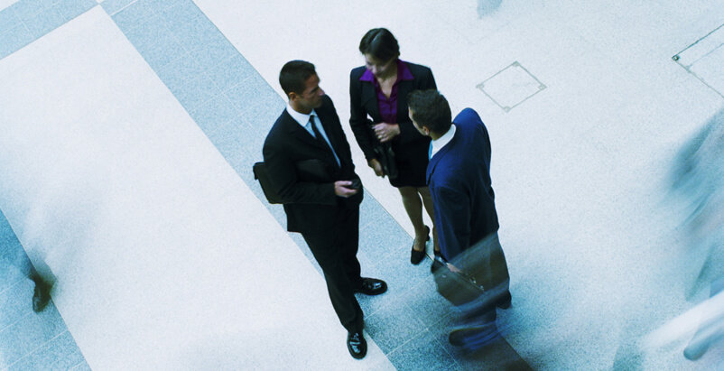 Bird's eye view of two men and a women dressed professionally standing up and talking