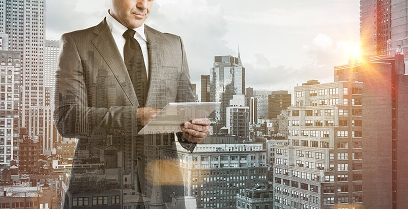 Man dressed professionally holding a tablet with buildings in the background
