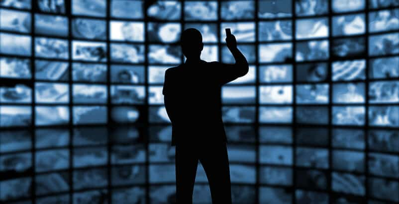 Silhouette of a person in front of multiple screens on a wall