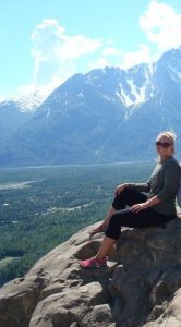 Julianne Krakowski sitting on a rock with mountains in the background