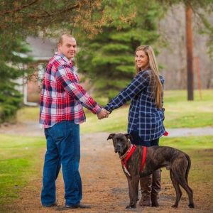 Julianne Krakowski and man holding hands with a dog outside
