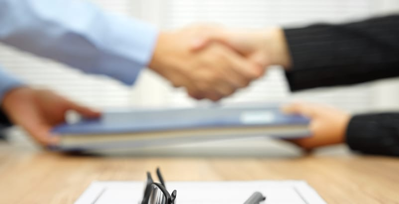 Blurry image of two people shaking hands and passing papers to each other over a table