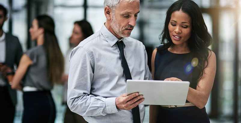 A man and woman looking at a tablet while standing up with people in the background