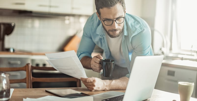 Man holding a coffee and sheet of paper looking over a laptop in the kitchen