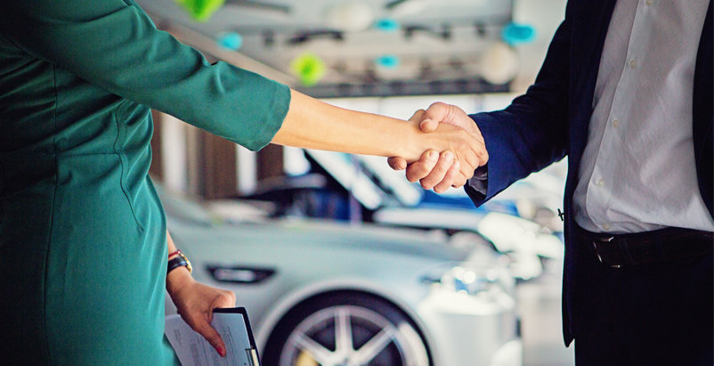 Two people shaking hands with a car in the background