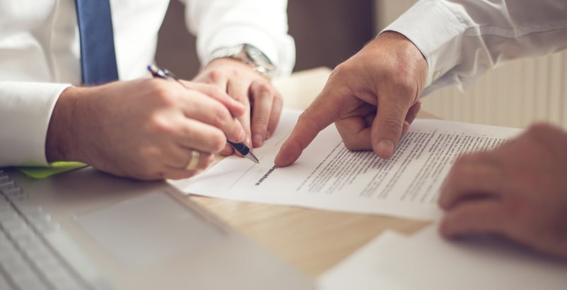 One person pointing where to sign, and the other person signing a form