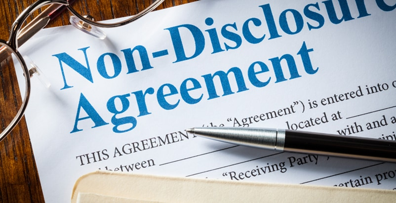 Close up of a Non-Disclosure Agreement paper and a pair of glasses on a table