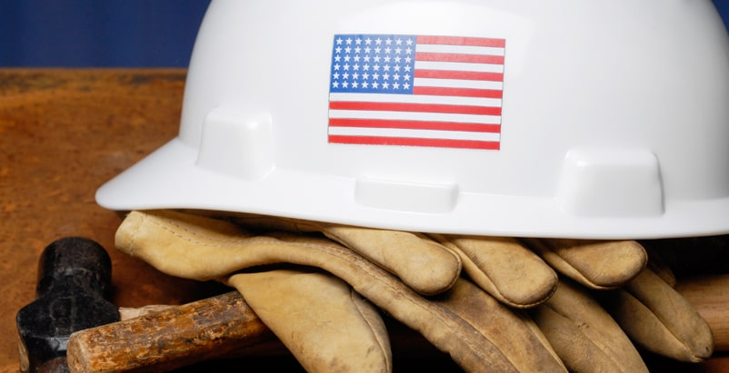 White hard hat with a United States flag on it laying on top of a pair of gloves and a hammer