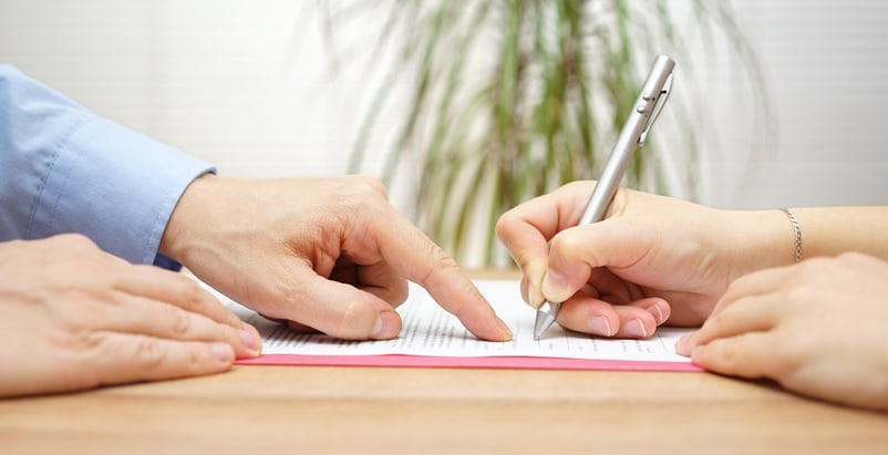 Person pointing at paper while other person is signing it with a pen at a table