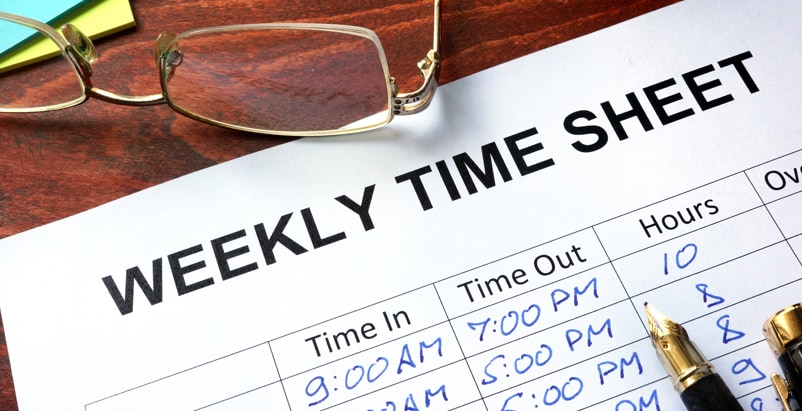 "Paper titled ""Weekly Time Sheet"" with times written in pen, a pen, and a pair of glasses on a table"