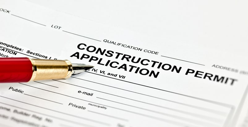 """Paper titled """"Construction Permit Application"""" with a pen pointing at it"""
