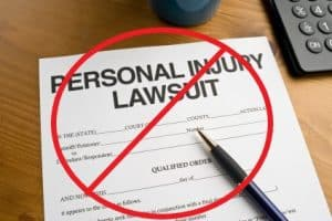 "Paper on a table titled ""Personal Injury Lawsuit"" with an illustration of a red crossed out circle over it"