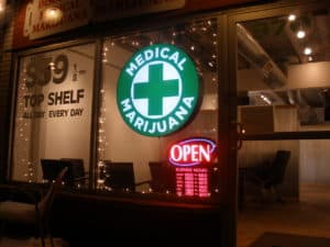 Front window of Medical Marijuana dispensary sign and open sign
